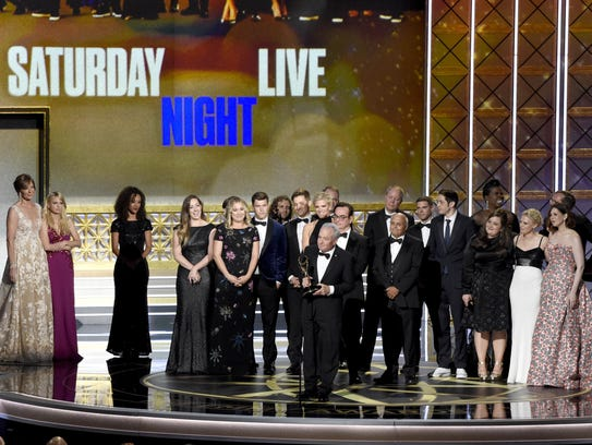 Lorne Michaels and the cast of SNL accept the award