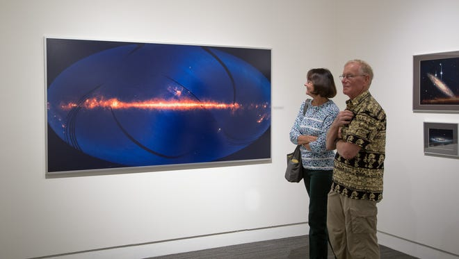 "Guests take in ""The History of Space Photography"" exhibit at the Foosaner Art Museum in Eau Gallie. The large photograph shows an image of nearly the entire heavens produced by the IRAS spacecraft."