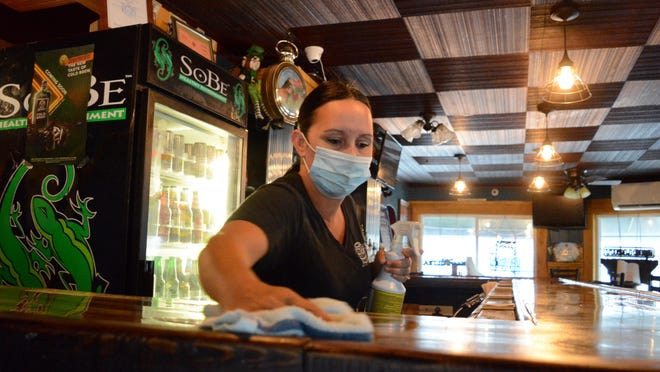 Darla Delia, a manager at McGill's Whiskey Tavern and Grill in Schuyler, wipes down the bar as she prepares to open to customers Friday.