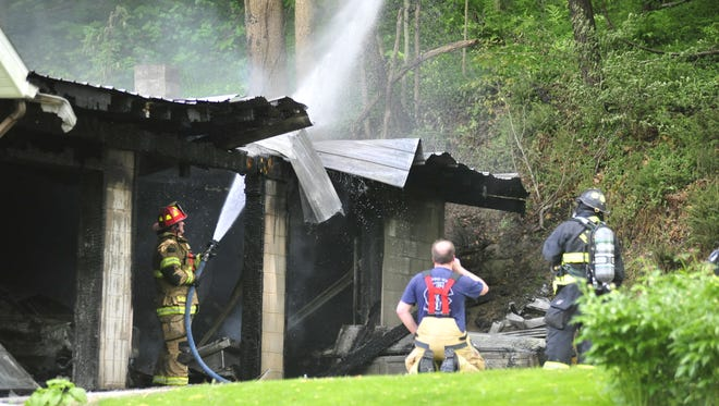 Firefighters finish putting out a garage fire Tuesday that likely started from a hot lawnmower.
