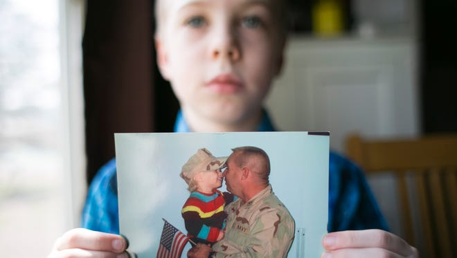 K.J. Yett, 10, holds a photograph of himself when he was two with his father, Robert Yett at his home in Cottonwood on Tuesday, August 12, 2014. After serving with the U.S. Navy during several tours in Iraq and Afghanistan, Robert Yett committed suicide in November of 2010. He was trying to seek treatment for his post traumatic stress disorder from the VA.