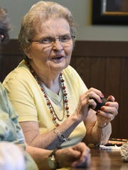 Jackie Conroy laughs with friends while shaking the cup of dice during the weekly game of Farkle on Tuesday at Country Manor Campus in Sartell.