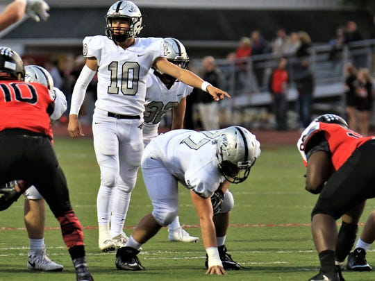 Stepping up to the line of scrimmage for Plymouth on Sept. 29 against Livonia Churchill is quarterback Zach Beadle (10).