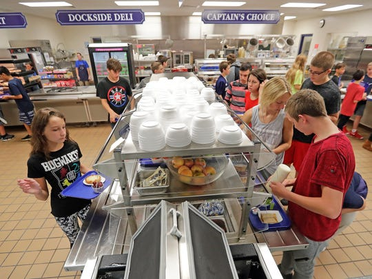 Students grab fruits and vegetables from the salad bar Tuesday at Bay View Middle School in Howard.