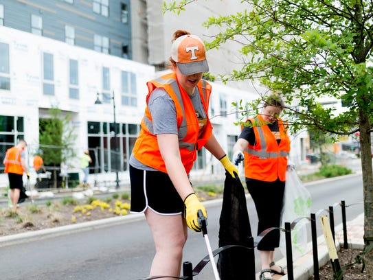 Heather Fawver, from Visit Knoxville, cleans up trash
