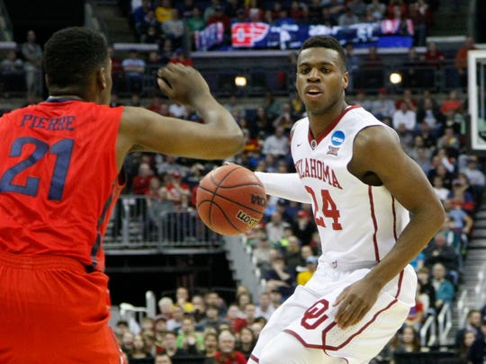 Oklahoma guard Buddy Hield is guarded by Dayton Flyers forward Dyshawn Pierre during the first half in the third round of the 2015 NCAA Tournament at Nationwide Arena.