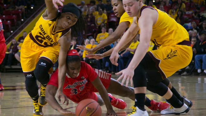 Arizona State's Elisha Davis and Sophie Brunner (21) dive for a loose ball against Arizona's JaLea Bennett (33) for a loose ball in the second half at Wells Fargo Arena in Tempe, AZ on January 22, 2016.