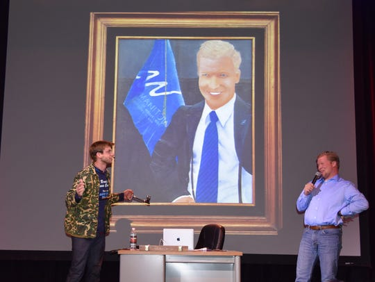 "Manitowoc Mayor Justin Nickels, right, and comedian Charlie Berens, creator of the popular online video series ""Manitowoc Minute,"" auction off an oil painting of Nickels on stage at the Capitol Civic Center in Manitowoc on Wednesday, Dec. 27, 2017. The painting was created by Brad Miller."