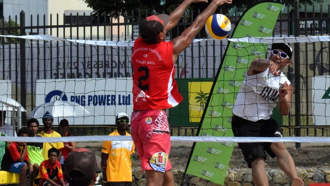 Guam men's national beach volleyball team member Shintaro Okada breaks a spike throught the net and the block during their match against No. 1 ranked Tahiti Monday at the Sir John Guise beach courts at the Pacific Games in Port Moresby, Papua New Guinea. Team Guam lost 21-11, 21-16.