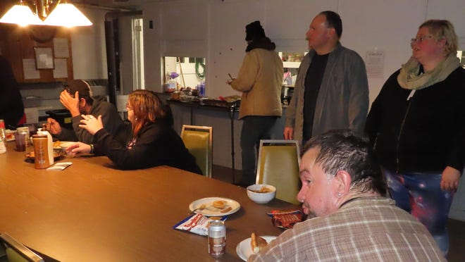 Volunteers and staff manning the Tri-State Interfaith Council's Warming Station offer guests a chance to shower and a hot meal on a cold winter night.