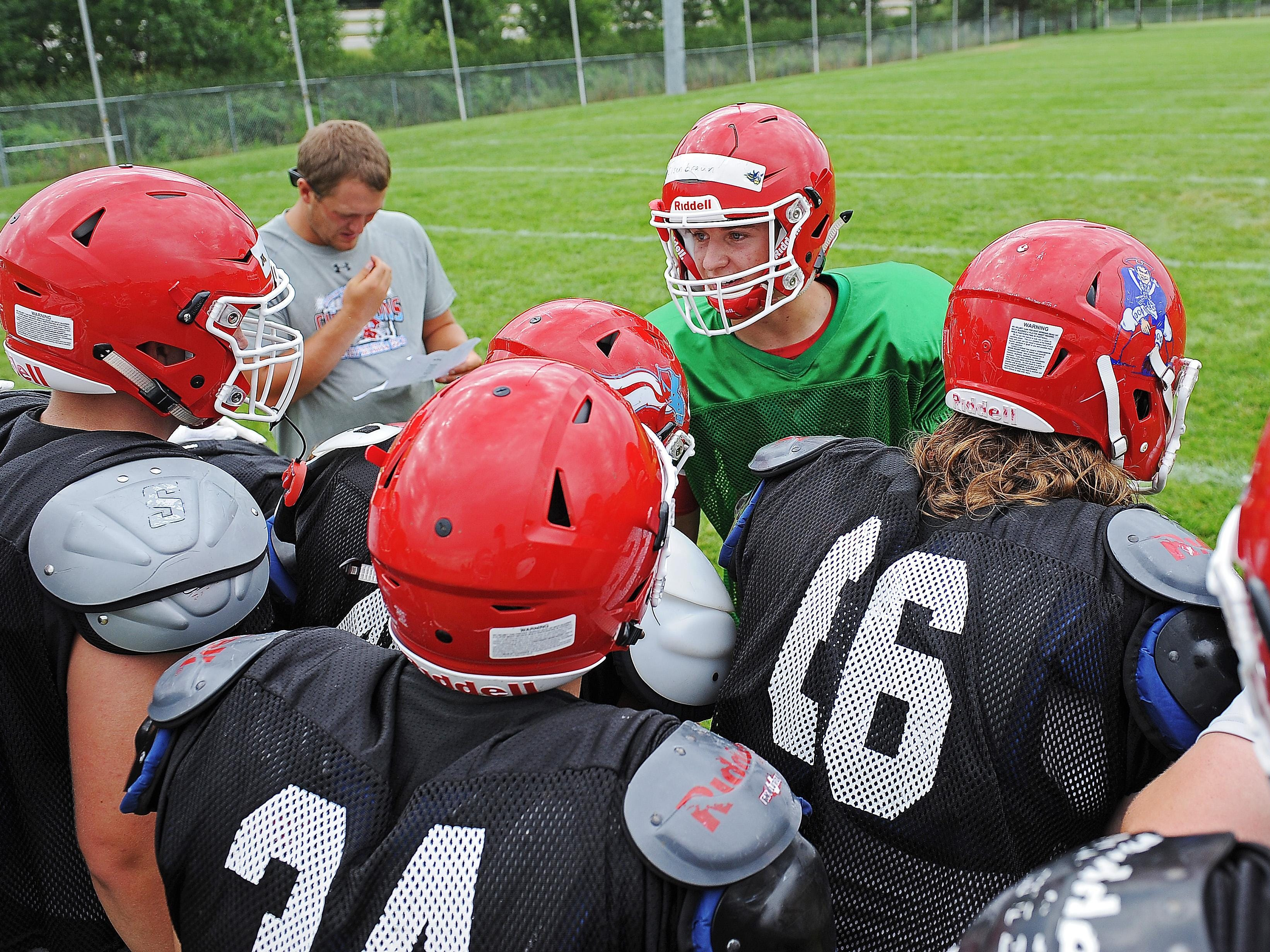 Lincoln quarterback Preston Eisenbraun talks to his teammates in a huddle during a Lincoln High School football practice Thursday, Aug. 11, 2016, at Lincoln High School in Sioux Falls.