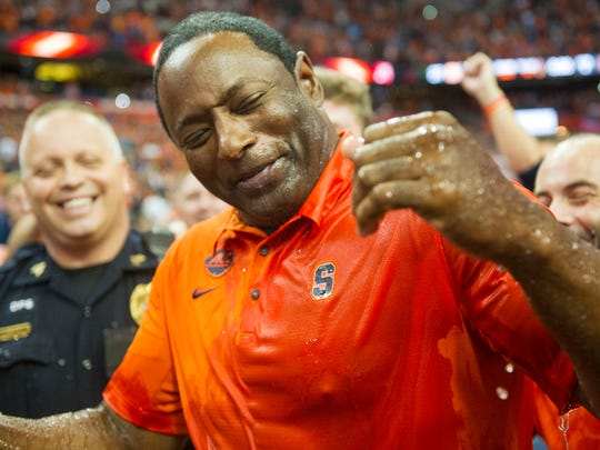 Syracuse coach Dino Babers reacts after being doused