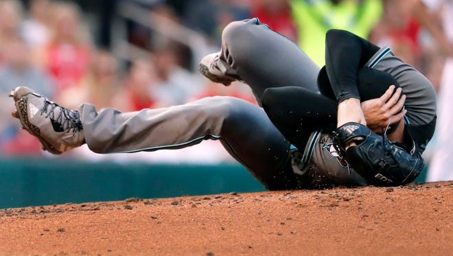 Arizona Diamondbacks starting pitcher Robbie Ray falls to the ground after being hit on the head by a ball back to the mound by St. Louis Cardinals' Luke Voit during the second inning of a baseball game Friday, July 28, 2017, in St. Louis. Ray left the game.