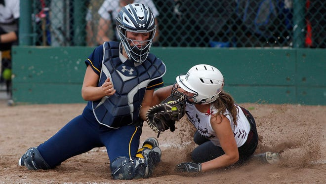 Webberville catcher Maci Kubiak, left, tags out Eaton Rapids' Elly Wythe at home plate Wednesday, May 17, 2017, at Ranney Park in Lansing, Mich.