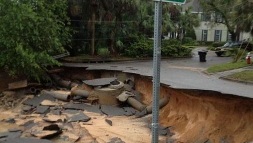 Floodwaters washes out a sections of the road at Lloyd and 20th Ave. in East Hill .