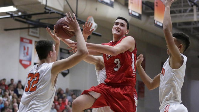 Kimberly's Will Chevalier gets between Kaukauna defenders on his way to the basket in a Fox Valley Association boys basketball game at Kaukauna High School last season.