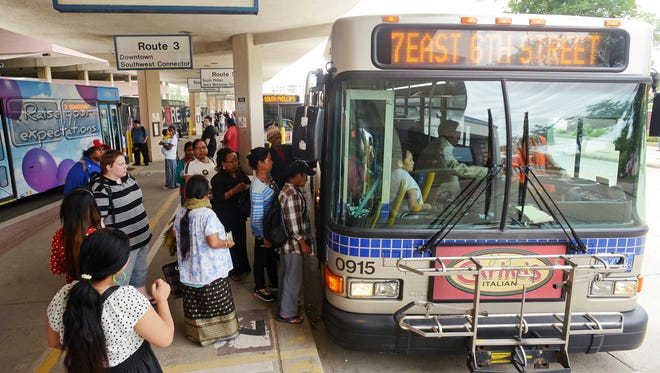Riders load onto a Route 7 bus Tuesday evening at the Sioux Area Metro downtown station in June.
