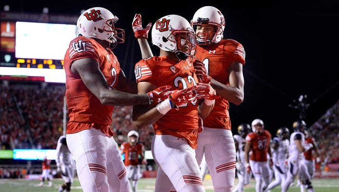 Utah running back Devontae Booker, center, celebrates with teammates after scoring a touchdown against California during the first half of an NCAA college football game Saturday, Oct. 10, 2015, in Salt Lake City. (Scott Sommerdorf/The Salt Lake Tribune via AP) DESERET NEWS OUT; LOCAL TELEVISION OUT; MAGS OUT; MANDATORY CREDIT