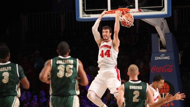 Wisconsin's Frank Kaminsky hits a reverse dunk as UAB's Chris Cokley (3), Lewis Sullivan (35) and Nick Norton (2) run in during their game in the Battle 4 Atlantis basketball tournament in Paradise Island, Bahamas, Wednesday Nov. 26, 2014.