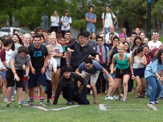 Willamette University students, staff and faculty try to come to a stop in the quad during an attempt to break the world record for participation in the game Red Light Green Light on Friday, Aug. 28, 2015.