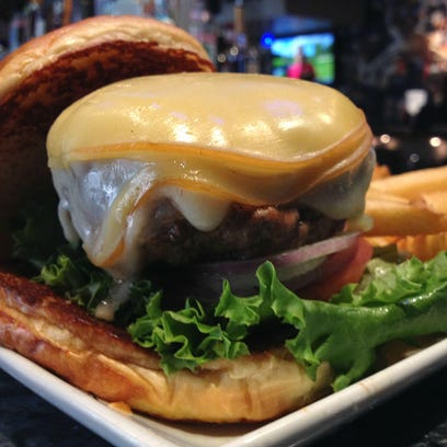 The Super Chesse-stuffed Burger is a half-pound burger filled with cheddar cheese and covered in Swiss and smoked Gouda cheeses at Colts Grille, one of eight restaurants competing in the Aug. 1 Indy Burger Battle.