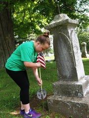 Third-grader Kimberly Croskey places a flag at a veteran's