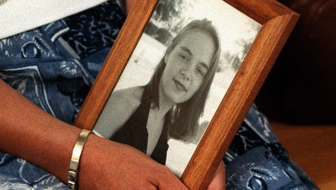 Rose Markey holds a photo of her daughter, Rose Larner in the Battle Creek courthouse in this 1996 file photo.