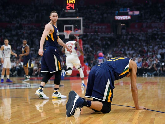 Utah Jazz center Rudy Gobert, of France, goes down after injuring his knee as forward Gordon Hayward looks back during the first half in Game 1 of an NBA basketball first-round playoff series against the Los Angeles Clippers, Saturday, April 15, 2017, in Los Angeles. (AP Photo/Mark J. Terrill)