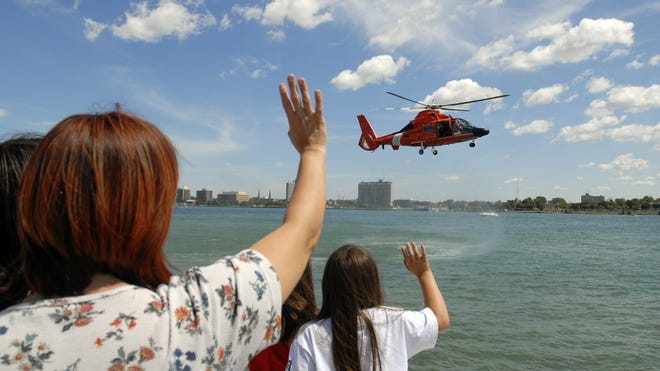 Melody Hartwig and Katie Julie, 10, and Gillian Hartwig, 7, all of Port Huron, wave to the helicopter crew after a water rescue demonstration, Saturday August 16, 2008, during Port Huron Coast Guard Days at Vantage Point.