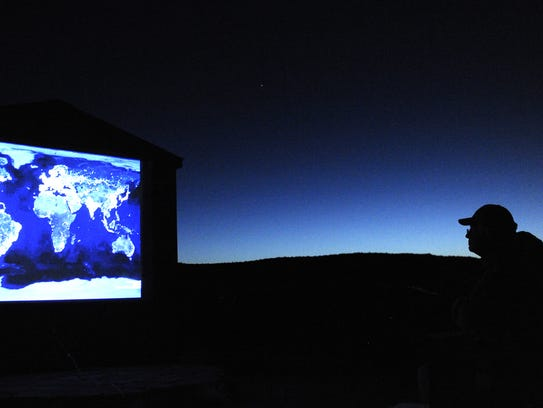 Tim Miller, of Durango, Colo., looks at a map of dark