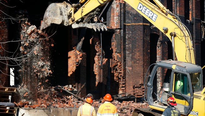 Crews demolish one of several brick pillars Tuesday at the Hesselson's warehouse on Prescott Avenue in Elmira Heights Sunday. Two 16-year-old males are accused of setting a fire on January 31 which caused the destruction.