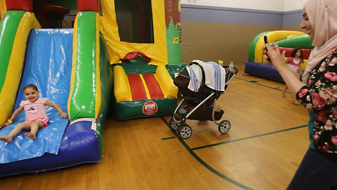 Kawther Mohammed, 26, of Dearborn photographs her daughter Sumayah Awad, 3, as she slides down an inflatable bounce house during the indoor Eid Carnival Sunday, July 18, 2015 at the school gym of the Islamic Center of America in Dearborn. The festival is inside due to the heat.