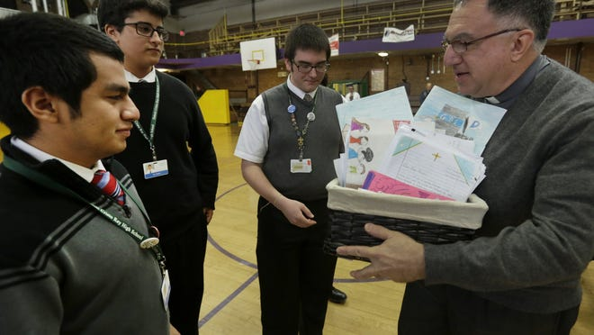 Left to right: Eduardo Garduno, Ali Alwan and Richard Straksys hand over a box of letters addressed to Pope Francis from Detroit-area Catholic school students, to the Rev. Thomas Rosica, a Vatican spokesman, Tuesday, Dec. 2, 2014.