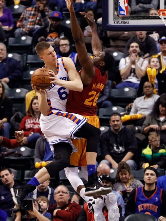 New York Knicks forward Kristaps Porzingis, left, passes around Indiana Pacers center Ian Mahinmi during the second half of an NBA basketball game in Indianapolis, Wednesday, Feb. 24, 2016. The Pacers won 108-105. (AP Photo/AJ Mast)