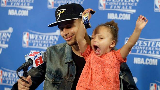 FILE - In this May 27, 2015, file photo, Golden State Warriors guard Stephen Curry is joined by his daughter Riley at a news conference after Game 5 of the NBA basketball Western Conference finals against the Houston Rockets in Oakland, Calif. (AP Photo/Ben Margot, File)