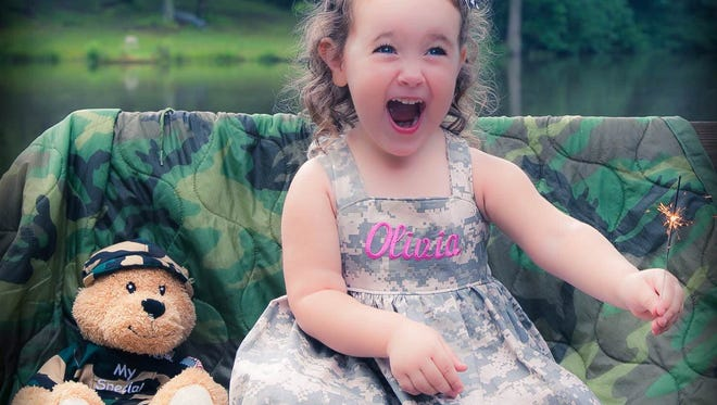 Olivia Hamilton, then three years old, greets her father in Fort Bragg as he returns from deployment. Her Henry Hero Bear kept her company while he was away.