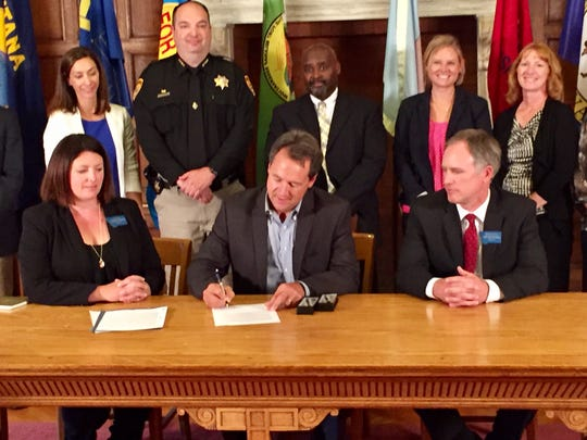 Gov. Steve Bullock, seated at center, does a ceremonial signing of crime bills Wednesday. Seated at left is Sen. Cynthia Wolken, D-Missoula.