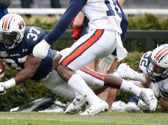 Auburn running back C.J. Tolbert, left, is tackled by defensive back Sam Sherrod, right, during the first half of the NCAA college football team's spring game Saturday, April 7, 2018, in Auburn, Ala. (AP Photo/Brynn Anderson)