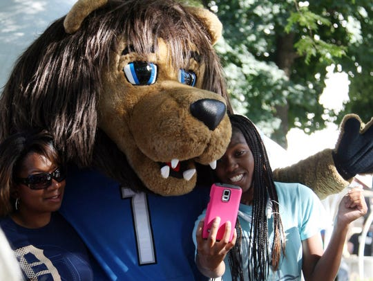 Lions mascot Roary poses with fans before a Lions game