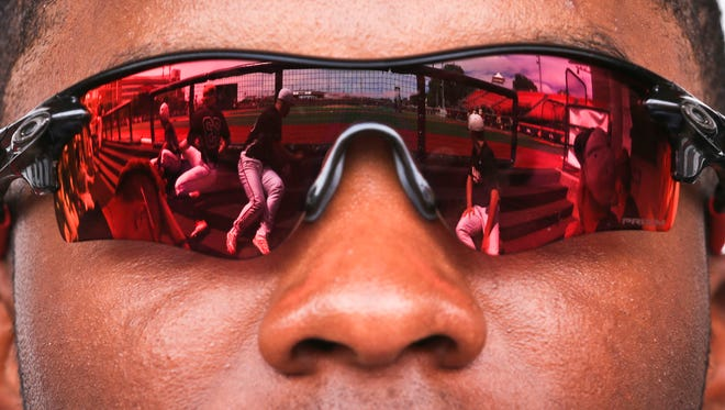 The baseball diamond and some of Josh Stowers teammates are reflected in the outfielder's sunglasses before the start of practice for the Louisville baseball team Monday. The Cardinals play in the ACC tournament Thursday.