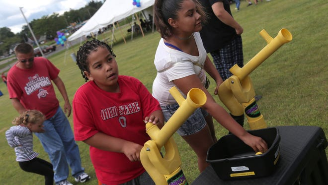 Jevon Keller, 9, and Evianna Bond, 12, play a game during the 150th anniversry celebration of the Mansfield YMCA on Saturday.