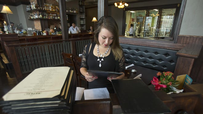 Samantha Schubert, a server at Repeal, reviews the evening's menu at the at a vintage, mahogany check desk Repeal owners Bill and Teresa Webster scored from another bank to use as a maitre d'stand.