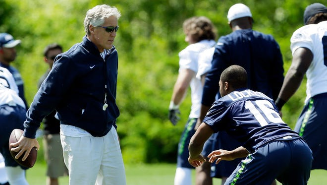 Seattle Seahawks head coach Pete Carroll, left, talks with rookie wide receiver Tyler Lockett, right, during NFL football rookie minicamp, Friday, May 8, 2015 in Renton, Wash.