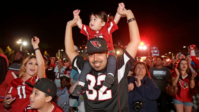 Cardinals fan Juan Navarro holds-up his 2-year-old daughter Scarlett Navarro as Robert Nkemdiche, defensive tackle from Mississippi was picked in the first round during the Cardinals Draft Party outside University of Phoenix Stadium in Glendale, Ariz., on Thursday, April 28, 2016.