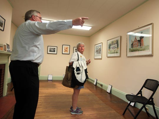 Dan Goodfriend points out artwork to Linda Barth of Somerville at the Friends of Fosterfields and Cooper Mill hosted Silent Art Auction at the Frelinghuysen Mansion.