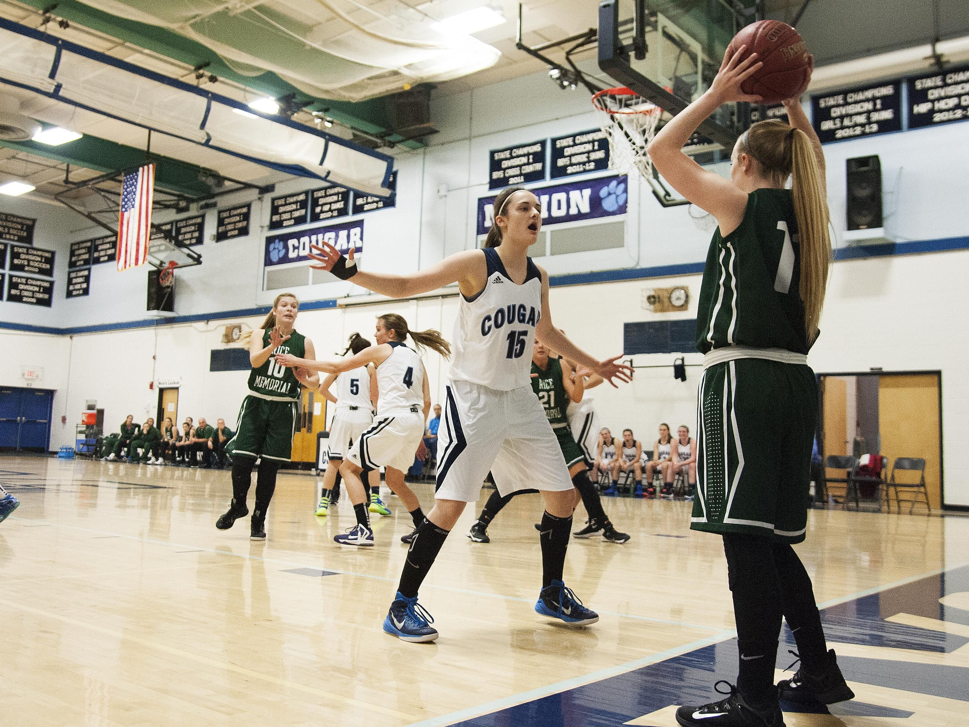 Mount Mansfield forward Lexi Mousley (15) guards Rice guard Jordan Lawrence (11) as she tries to throw the ball in bounds during the girls basketball game between the Rice Green knights and the Mount Mansfield Cougars at MMU High School on Friday night December 4, 2015 in Jericho.