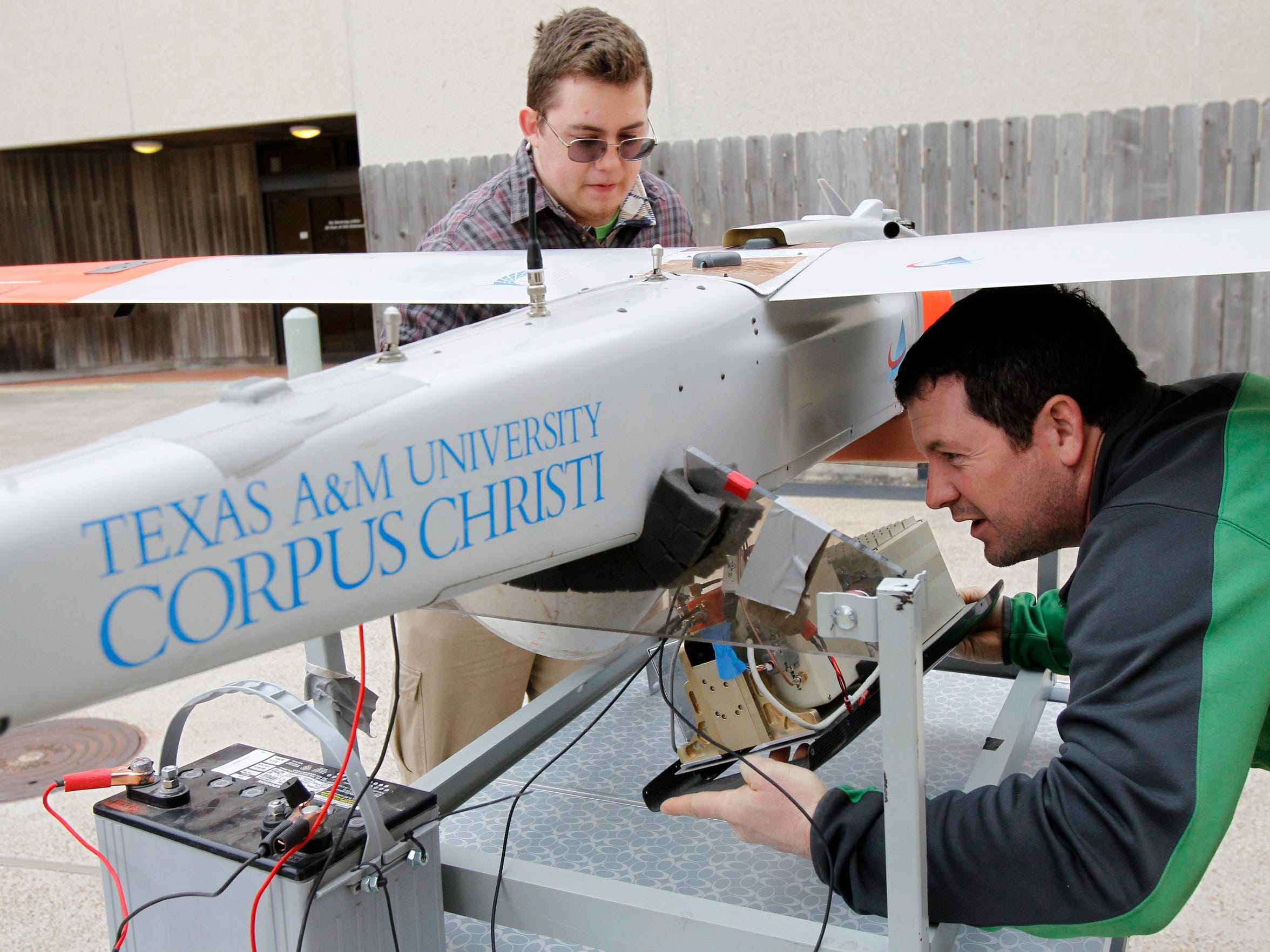 Freshman Martin Hass of Austin (left) looks on as Anthony Di Stefano, field application engineer for American Aerospace, pulls out the cameras and on-board computer on Dec. 11, 2013 as they try to configure the unmanned aerial vehicle at Texas A&M University-Corpus Christi.
