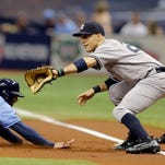 Tampa Bay Rays' Brad Miller (13) dives back to first base ahead of the tag by New York Yankees first baseman Dustin Ackley during the first inning of a baseball game Sunday, May 29, 2016, in St. Petersburg, Fla.