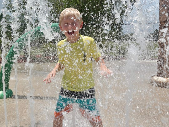 Austin Astrup, 6, cools off in the splash pad at the