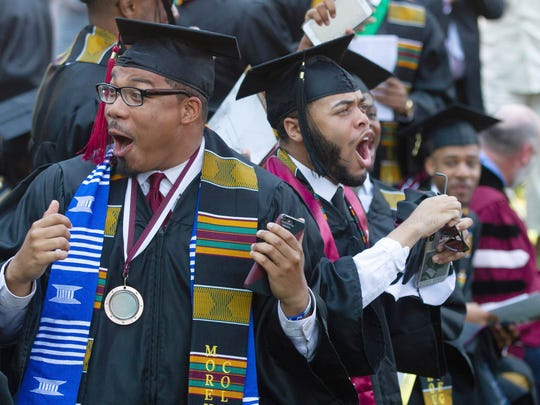 Graduates react after hearing billionaire technology investor and philanthropist Robert F. Smith say he will provide grants to wipe out the student debt of their entire graduating class at Morehouse College in Atlanta on Sunday.